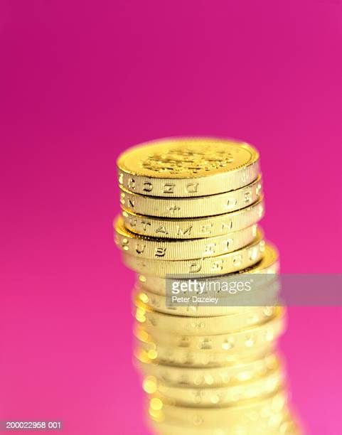 UK Currency: Stacked one pound coins against pink background, close-up