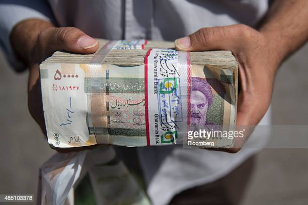 A currency trader holds a large bundle of rial banknotes outside a bazaar in this arranged photograph in Tehran Iran on Saturday Aug 22 2015 Iran...
