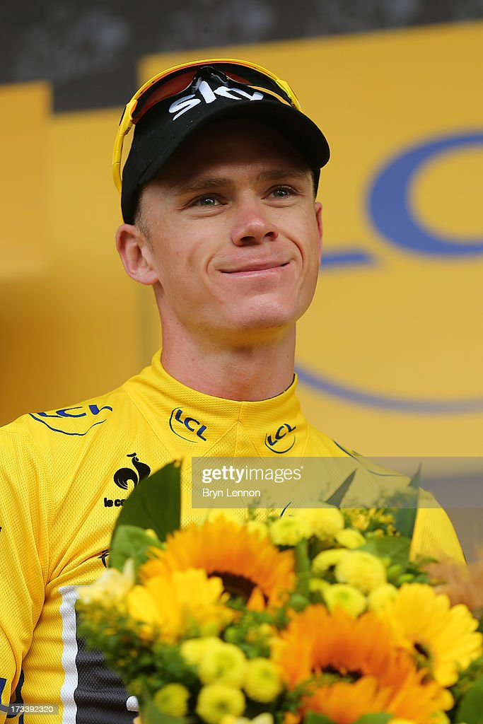 Current race leader and wearer of the Maillot Jaune, Chris Froome of Great Britain and SKY Procycling (C) celebrates on the podium after stage fourteen of the 2013 Tour de France, a 191KM road stage from Saint-Pourcain-sur-Sioule to Lyon, on July 13, 2013 in Lyon, France.