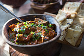 A wooden serving dish filled with lamb curry and rootis, a heartwarming and fragrant traditionally Indian meal.