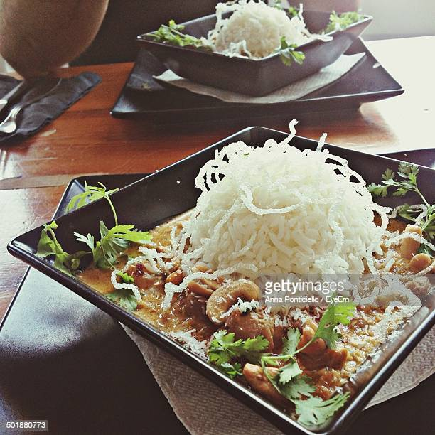 Curry chicken with rice served in plate at table