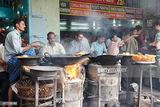 Curry dishes cooking under outdoor fires Indian street scene