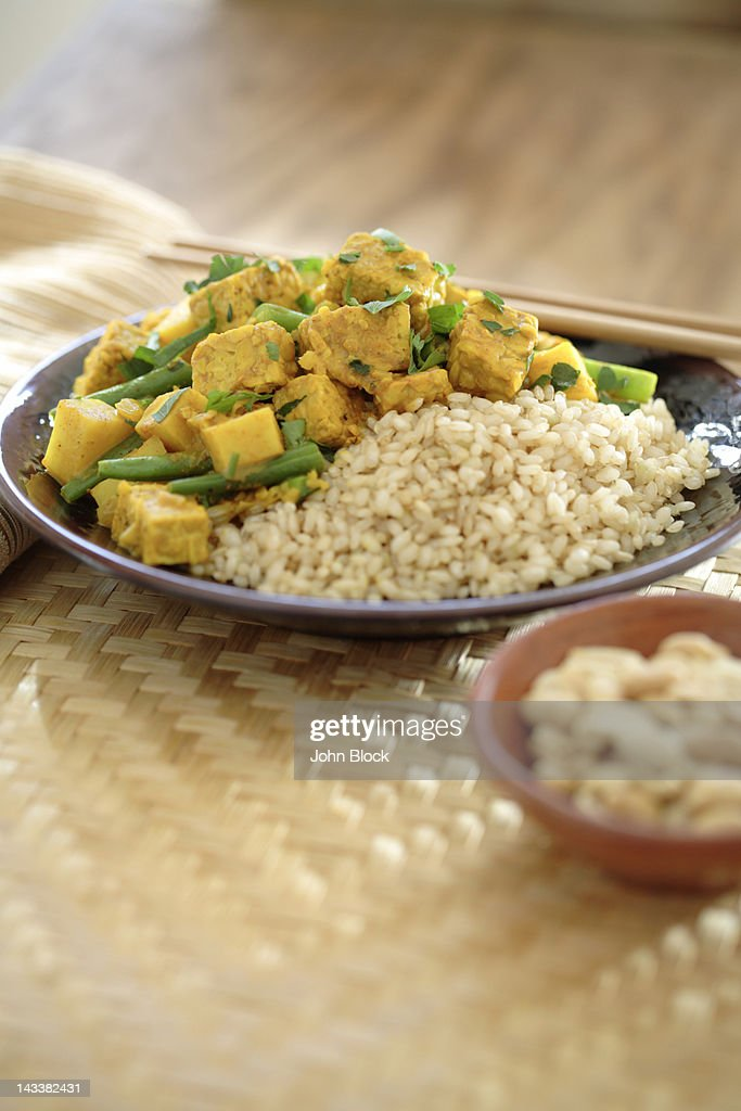 Curry soy tempeh and rice in bowl : Stock Photo