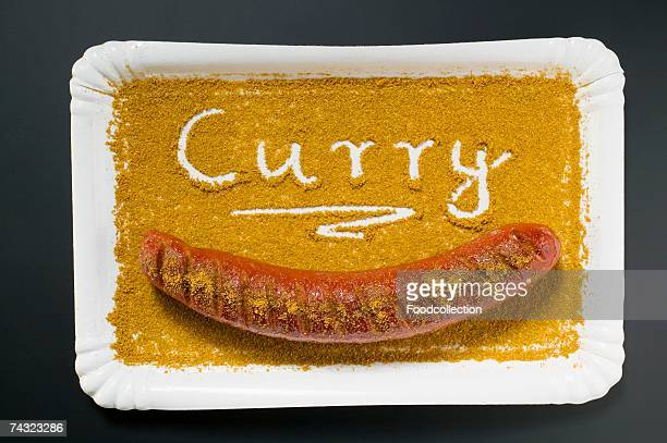 A currywurst in curry powder on a paper plate