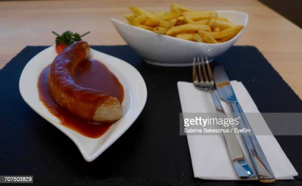 Currywurst With Ketchup By Fries In Bowl In Plate On Table