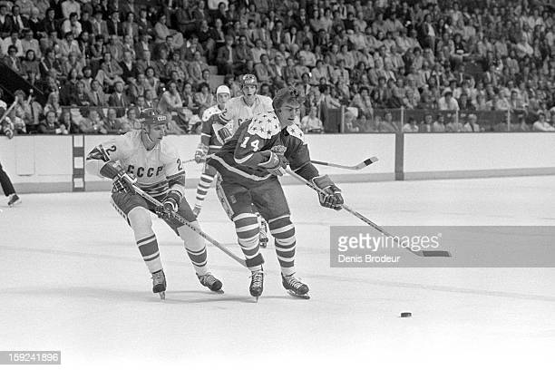 Curt Bennett of the USA handles the puck against Alexander Gusev of the Soviet Union looks on during a Canada Cup game at the Philadelphia Spectrum...