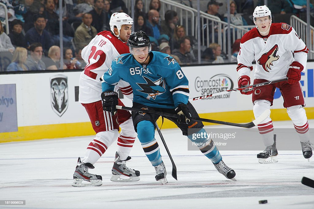 Curt Gogol of the San Jose Sharks skates after the puck against Brandon Yip of the Phoenix Coyotes during a preseason NHL game at SAP Center on...