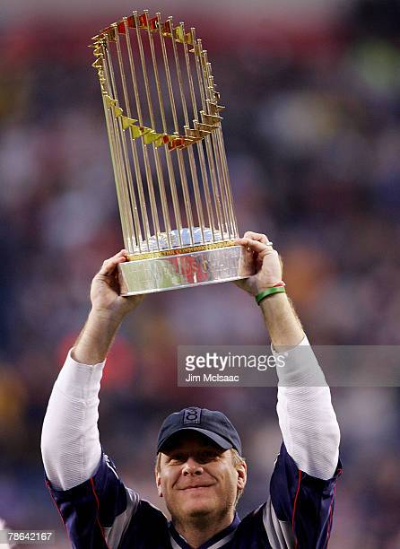Curt Schilling of the Boston Red Sox holds up the World Series trophy before the game between the New England Patriots and the Miami Dolphins at...
