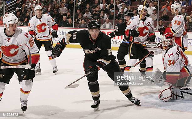 Curtis Giencross and Miikka Kiprusoff of the Calgary Flames watch Bobby Ryan of the Anaheim Ducks move to the puck during the game on February 11...