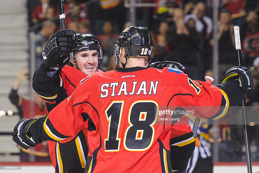 Curtis Glencross #20 of the Calgary Flames celebrates scoring his team's fifth goal against the Washington Capitals along with his teammate Matt Stajan #18 during an NHL game at Scotiabank Saddledome on October 26, 2013 in Calgary, Alberta, Canada. The Flames defeated the Capitals 5-2.