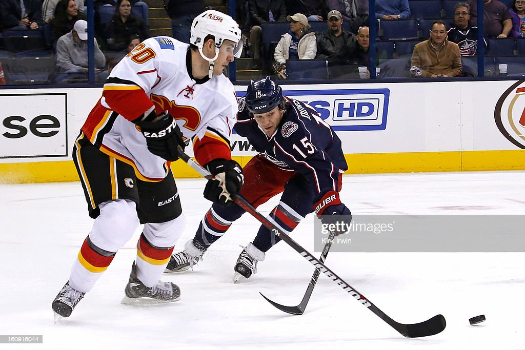Curtis Glencross #20 of the Calgary Flames clears the puck away from Derek Dorsett #15 of the Columbus Blue Jackets during the third period on February 7, 2013 at Nationwide Arena in Columbus, Ohio. Calgary defeated Columbus 4-3 in overtime.