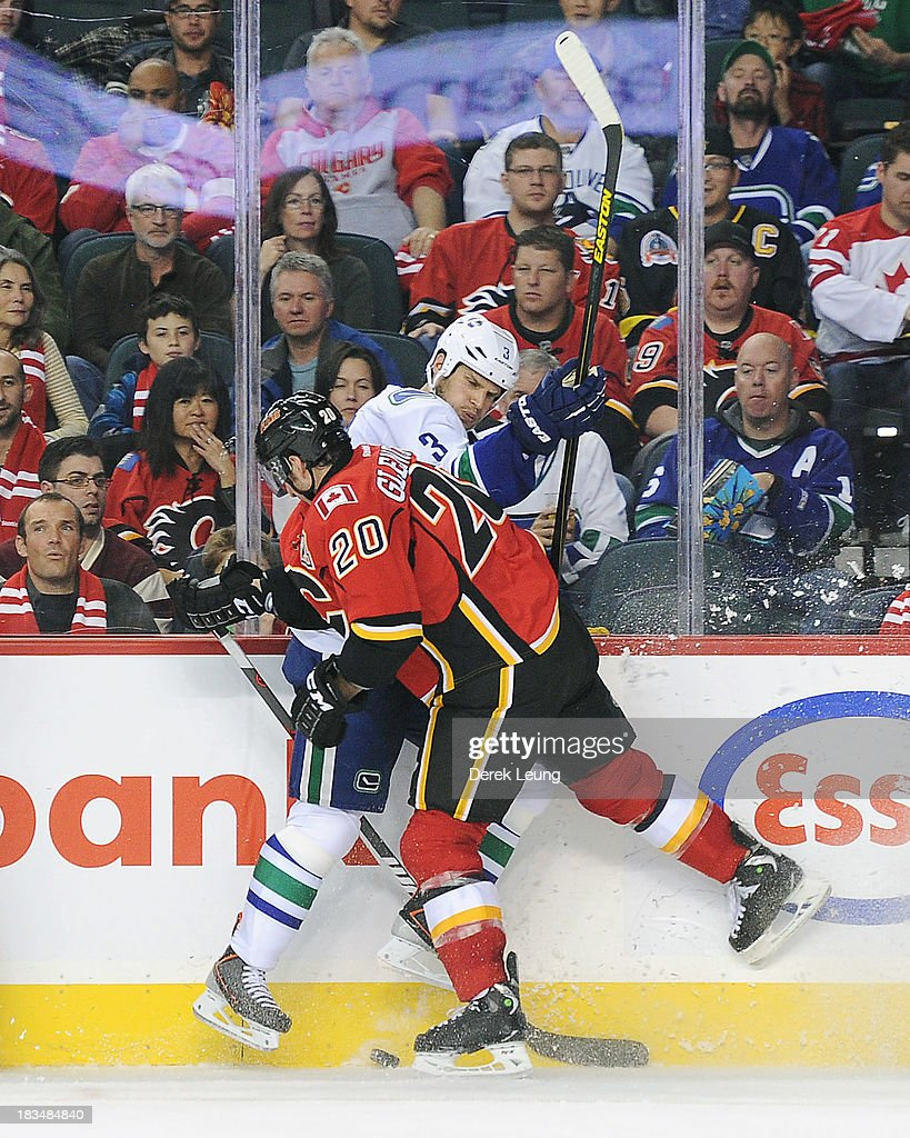 <a gi-track='captionPersonalityLinkClicked' href=/galleries/search?phrase=Curtis+Glencross&family=editorial&specificpeople=2190970 ng-click='$event.stopPropagation()'>Curtis Glencross</a> #20 of the Calgary Flames collides with <a gi-track='captionPersonalityLinkClicked' href=/galleries/search?phrase=Kevin+Bieksa&family=editorial&specificpeople=688792 ng-click='$event.stopPropagation()'>Kevin Bieksa</a> #3 of the Vancouver Canucks during the Flames' home opening NHL game at Scotiabank Saddledome on October 6, 2013 in Calgary, Alberta, Canada. The Vancouver Canucks won 5-4 in OT.