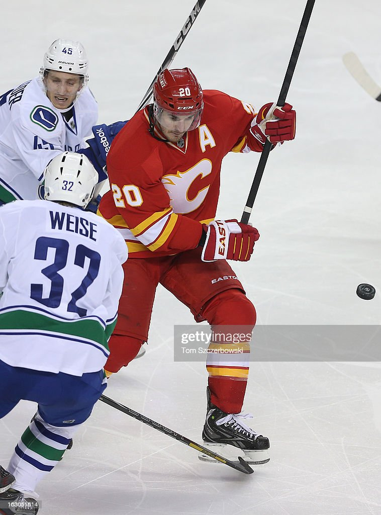 Curtis Glencross #20 of the Calgary Flames keeps his eye on a bouncing puck during their NHL game as Jordan Schroeder #45 of the Vancouver Canucks checks him at the Scotiabank Saddledome on March 3, 2013 in Calgary, Alberta, Canada.