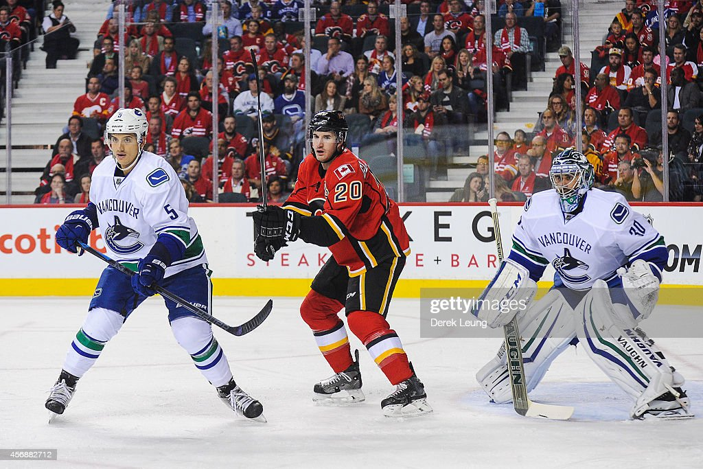 Curtis Glencross of the Calgary Flames looks for an opportunity as Luca Sbisa and Ryan Miller of the Vancouver Canucks defend during an NHL game at...