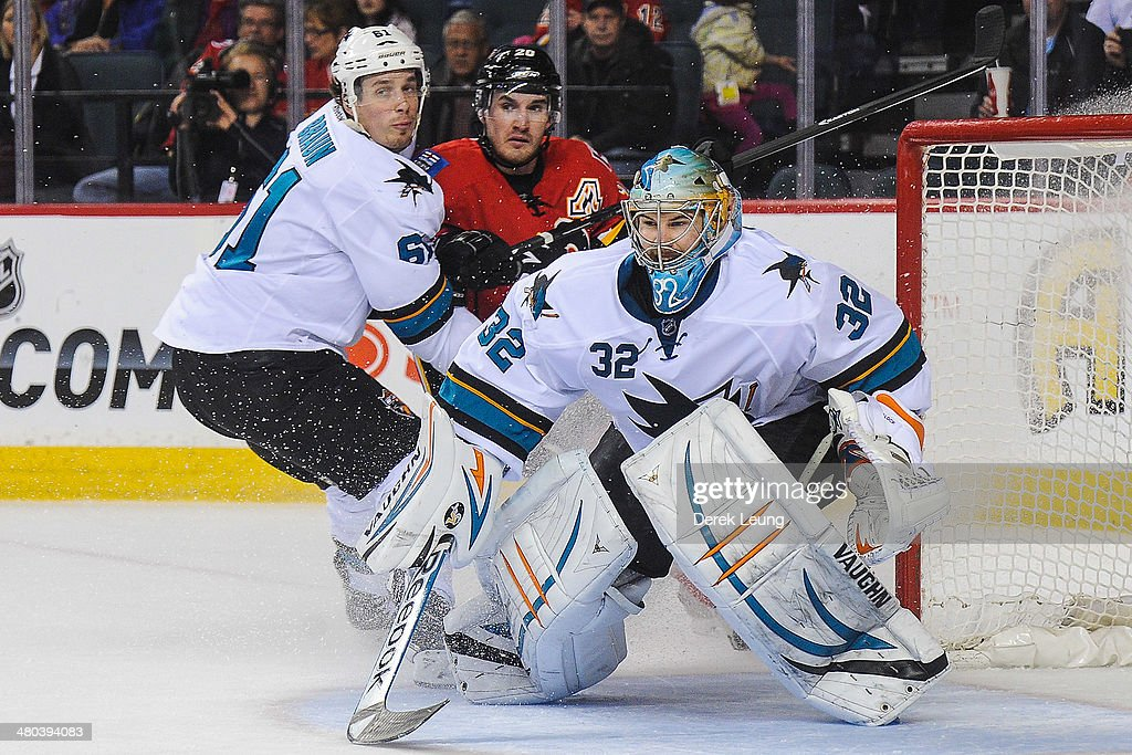 Curtis Glencross #20 of the Calgary Flames looks for an opportunity as Justin Braun #61 (L) and Alex Stalock #32 of the San Jose Sharks defend during an NHL game at Scotiabank Saddledome on March 24, 2014 in Calgary, Alberta, Canada. The Flames defeated the Sharks 2-1 in shootout.