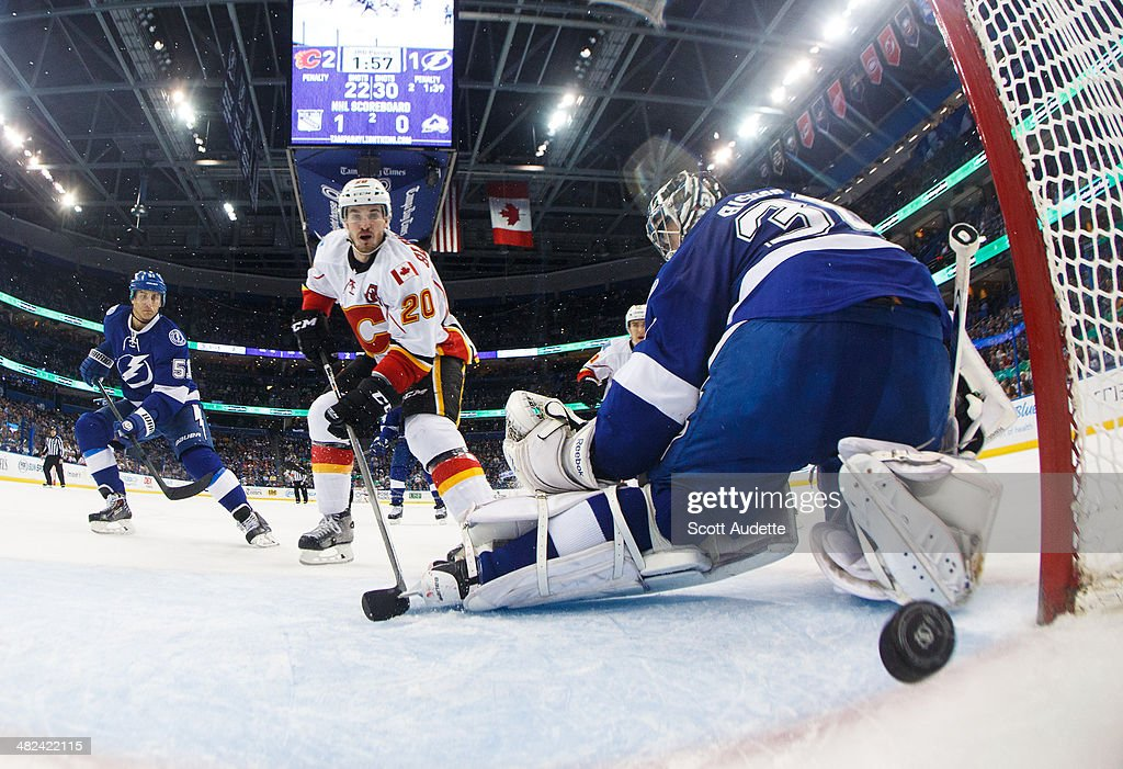 <a gi-track='captionPersonalityLinkClicked' href=/galleries/search?phrase=Curtis+Glencross&family=editorial&specificpeople=2190970 ng-click='$event.stopPropagation()'>Curtis Glencross</a> #20 of the Calgary Flames shoots the puck by goalie <a gi-track='captionPersonalityLinkClicked' href=/galleries/search?phrase=Ben+Bishop&family=editorial&specificpeople=700137 ng-click='$event.stopPropagation()'>Ben Bishop</a> #30 during the third period at the Tampa Bay Times Forum on April 3, 2014 in Tampa, Florida.