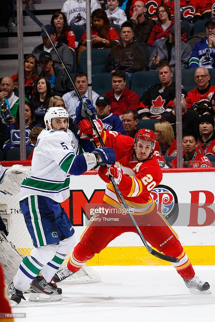 <a gi-track='captionPersonalityLinkClicked' href=/galleries/search?phrase=Curtis+Glencross&family=editorial&specificpeople=2190970 ng-click='$event.stopPropagation()'>Curtis Glencross</a> #20 of the Calgary Flames skates against <a gi-track='captionPersonalityLinkClicked' href=/galleries/search?phrase=Jason+Garrison&family=editorial&specificpeople=2143635 ng-click='$event.stopPropagation()'>Jason Garrison</a> #5 of the Vancouver Canucks on March 3, 2013 at the Scotiabank Saddledome in Calgary, Alberta, Canada.