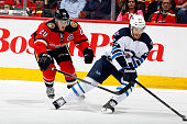Curtis Glencross of the Calgary Flames skates against Zach Redmond of the Winnipeg Jets at Scotiabank Saddledome on April 11 2014 in Calgary Alberta...