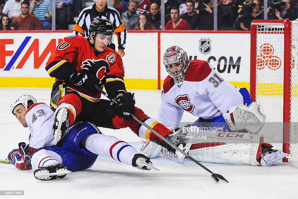 Curtis Glencross of the Calgary Flames tries to control the puck after being knocked off his feet by Mike Weaver of the Montreal Canadiens during an...