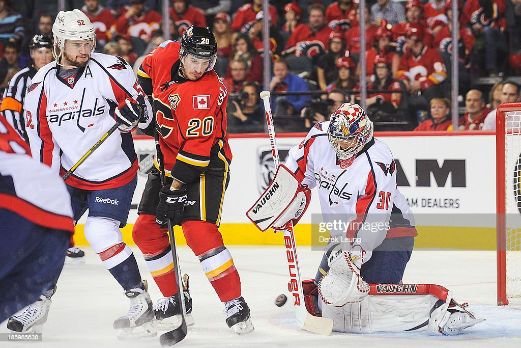 Curtis Glencross #20 of the Calgary Flames tries to deflect the puck as Michal Neuvirth #30 of the Washington Capitals defends during an NHL game at Scotiabank Saddledome on October 26, 2013 in Calgary, Alberta, Canada. The Flames defeated the Capitals 5-2.