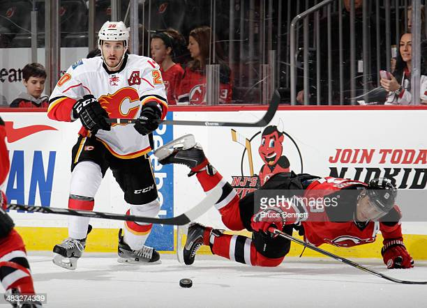 Curtis Glencross of the Calgary Flames trips up Dainius Zubrus of the New Jersey Devils during the first period at the Prudential Center on April 7...