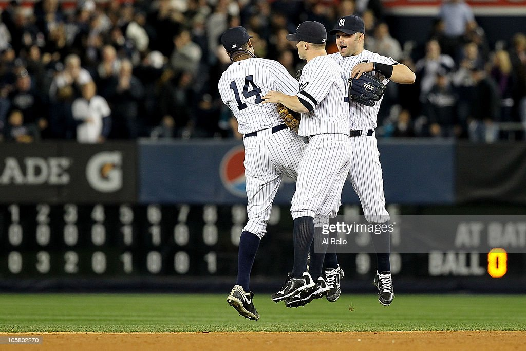 Curtis Granderson #14, Brett Gardner #11 and Nick Swisher #33 of the New York Yankees celebrate after the Yankees won 7-2 against the Texas Rangers in Game Five of the ALCS during the 2010 MLB Playoffs at Yankee Stadium on October 20, 2010 in the Bronx borough of New York City.