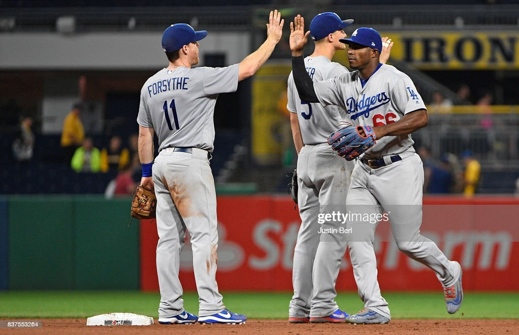 Curtis Granderson #6 of the Los Angeles Dodgers high fives with Logan Forsythe #11 after the final out in the Los Angeles Dodgers 8-5 win over the Pittsburgh Pirates at PNC Park on August 22, 2017 in Pittsburgh, Pennsylvania.