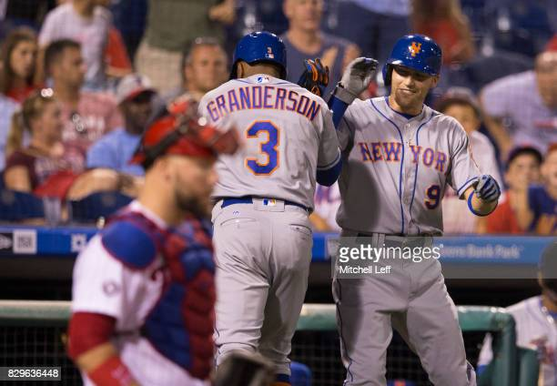 Curtis Granderson of the New York Mets celebrates with Brandon Nimmo in front of Cameron Rupp of the Philadelphia Phillies after hitting a two run...