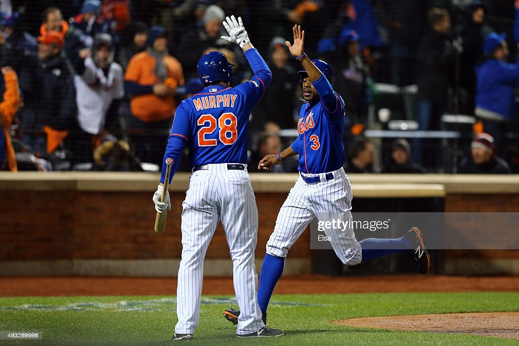 Curtis Granderson of the New York Mets celebrates with Daniel Murphy after scoring a run off of a double hit by David Wright in the first inning...