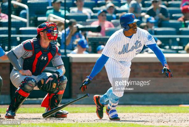 Curtis Granderson of the New York Mets follows through on a seventh inning RBI single as Matt Wieters of the Washington Nationals looks on at Citi...
