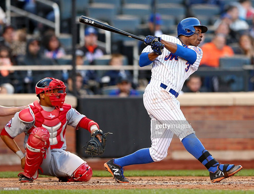 Curtis Granderson of the New York Mets hits a solo home run in the eighth inning as Pedro Severino of the Washington Nationals defends on October 4...