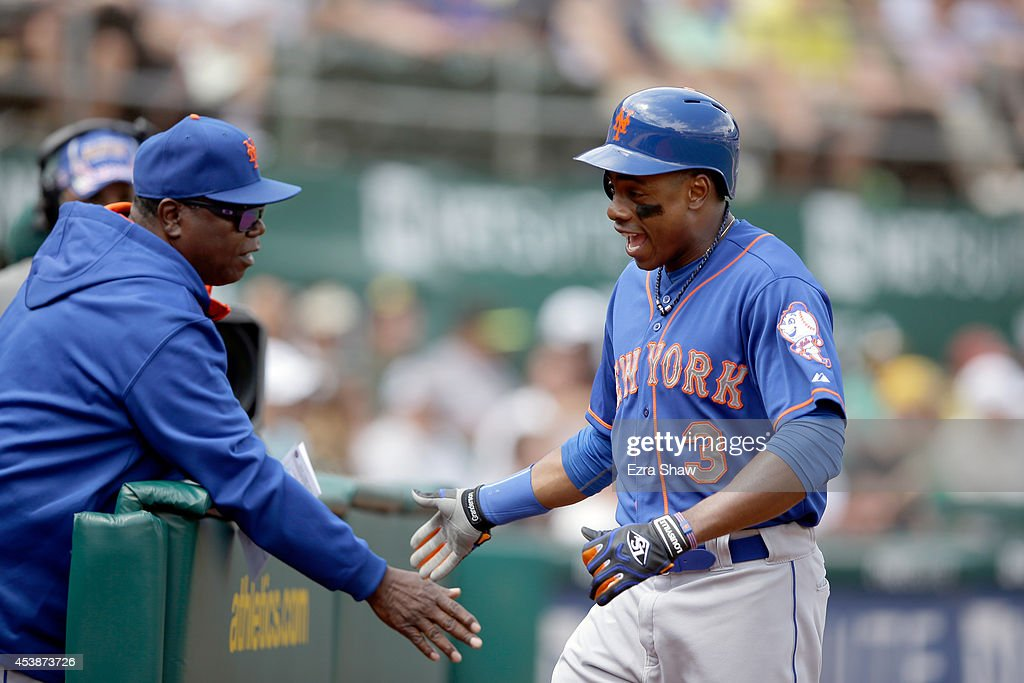 <a gi-track='captionPersonalityLinkClicked' href=/galleries/search?phrase=Curtis+Granderson&family=editorial&specificpeople=546997 ng-click='$event.stopPropagation()'>Curtis Granderson</a> #3 of the New York Mets is congratulated by teammates after he scored on a wild pitch by Jeff Samardzija #29 of the Oakland Athletics in the third inning at O.co Coliseum on August 20, 2014 in Oakland, California.