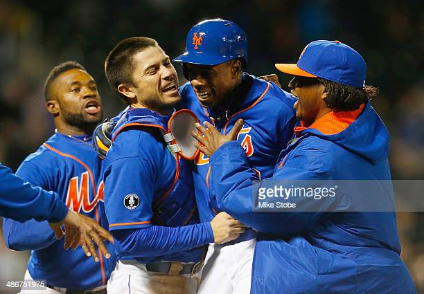Curtis Granderson of the New York Mets is mobbed by Travis d'Arnaud and Jenrry Mejia after hitting a walk off single in the bottom of the ninth...