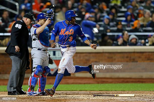 Curtis Granderson of the New York Mets scores a run off of an RBI infield single hit by Yoenis Cespedes in the third inning against Jake Arrieta of...