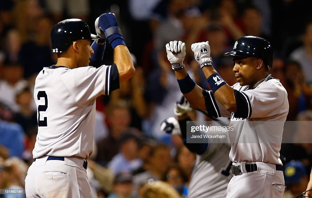 Curtis Granderson #14 of the New York Yankees is congratulated by teammate Derek Jeter #2 after hitting his second home run of the game in the 7th inning against the Boston Red Sox during the game on September 12, 2012 at Fenway Park in Boston, Massachusetts.