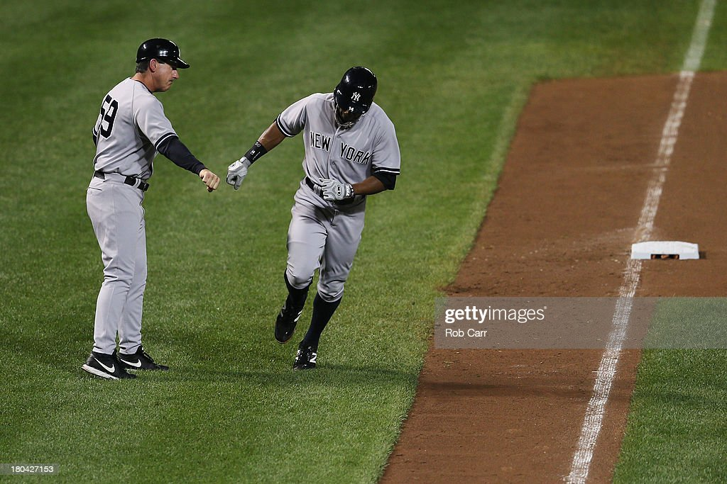 Curtis Granderson #14 of the New York Yankees is congratulated by third base coach Rob Thomson after hitting a solo home run against the Baltimore Orioles during the seventh inning at Oriole Park at Camden Yards on September 12, 2013 in Baltimore, Maryland.