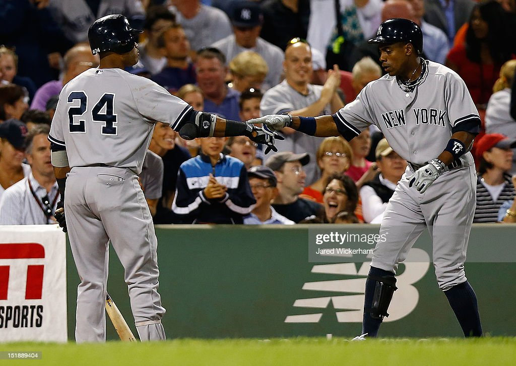 Curtis Granderson #14 of the New York Yankees is congratulted by teammate Robinson Cano #24 after hitting a solo home run in the fourth inning against the Boston Red Sox during the game on September 12, 2012 at Fenway Park in Boston, Massachusetts.