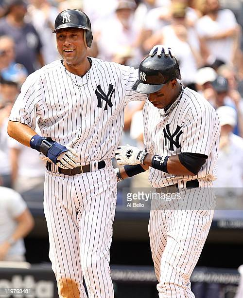 Curtis Granderson of the New York Yankees is met by Derek Jeter after he hit a two run home run in the fifth inning against the Oakland Athletics...
