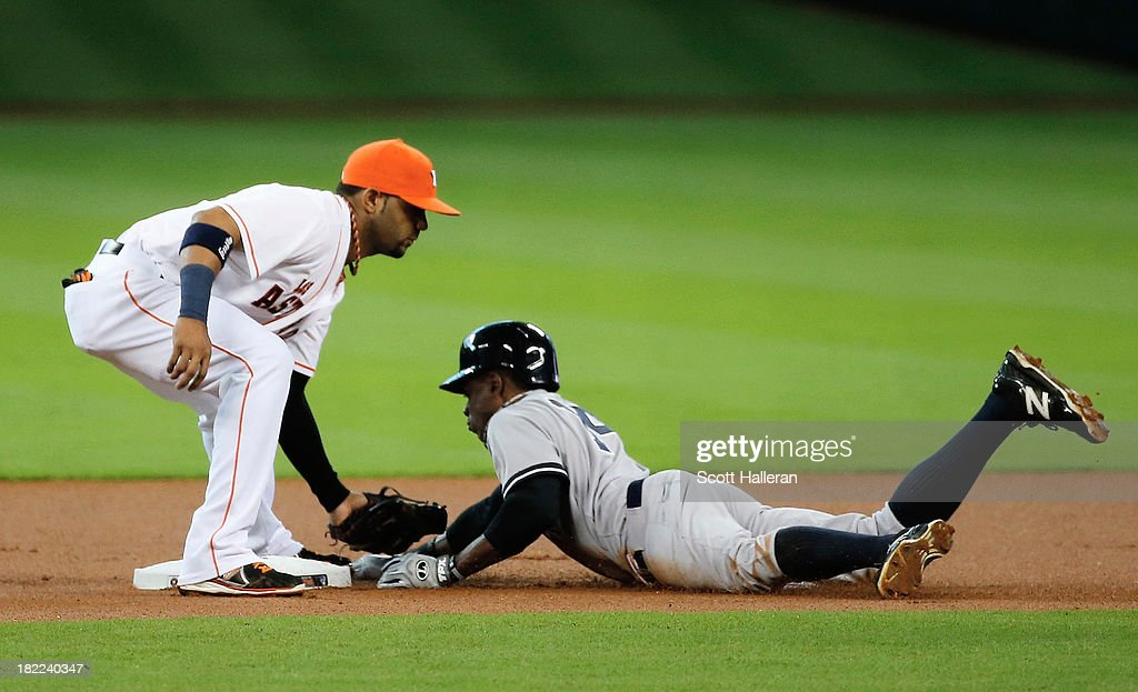 Curtis Granderson #14 of the New York Yankees is tagged out at second base in the first inning by Jonathan Villar #6 of the Houston Astros at Minute Maid Park on September 28, 2013 in Houston, Texas.
