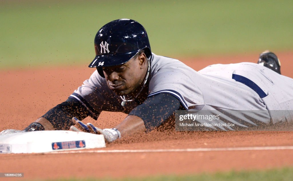 Curtis Granderson #14 of the New York Yankees slides into third after advancing on a wild throw against the Boston Red Sox in the first inning on September 15, 2013 at Fenway Park in Boston Massachusetts.