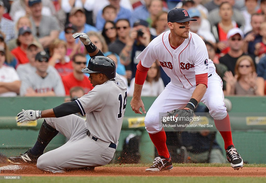 Curtis Granderson #14 of the New York Yankees slides into third with a triple ahead of a throw to Will Middlebrooks #16 of the Boston Red Sox in the fourth inning on September 14, 2013 at Fenway Park in Boston Massachusetts.