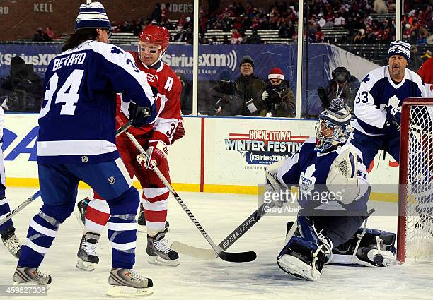 Curtis Joseph of the Toronto Maple Leafs Alumni is scored on by Kris Draper of the Detroit Red Wings Alumni during game action on December 31 2013 at...