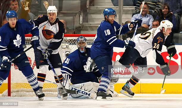 Curtis Joseph of the Toronto Maple Leafs keeps his eyes on the puck as teammates Dominic Moore and Luke Schenn battle in front of the net with Colby...