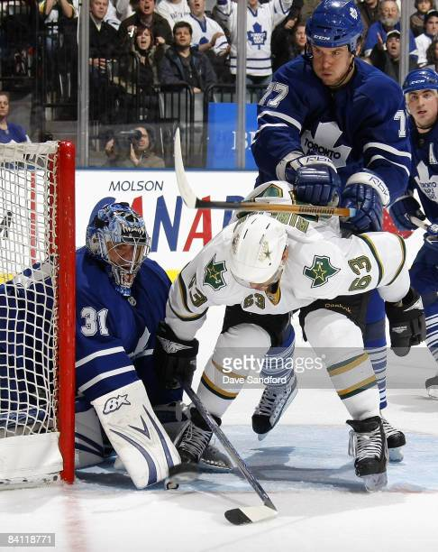 Curtis Joseph of the Toronto Maple Leafs makes a save as teammate Pavel Kubina checks Mike Ribeiro of the Dallas Stars during their NHL game at the...