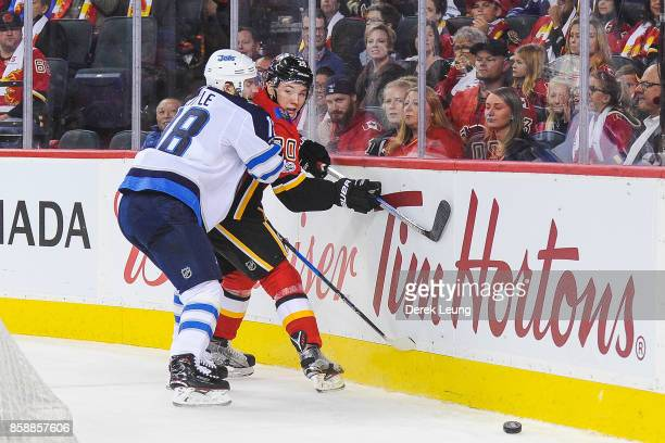 Curtis Lazar of the Calgary Flames gets checked by Bryan Little of the Winnipeg Jets during an NHL game at Scotiabank Saddledome on October 7 2017 in...