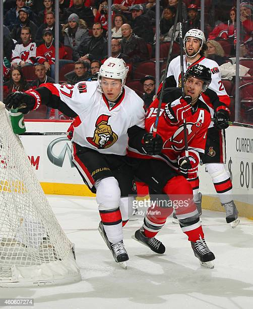 Curtis Lazar of the Ottawa Senators and Travis Zajac of the New Jersey Devils battle for position during the game at the Prudential Center on...