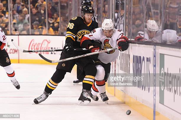 Curtis Lazar of the Ottawa Senators fights for the puck against Kevan Miller of the Boston Bruins at the TD Garden on December 13 2014 in Boston...