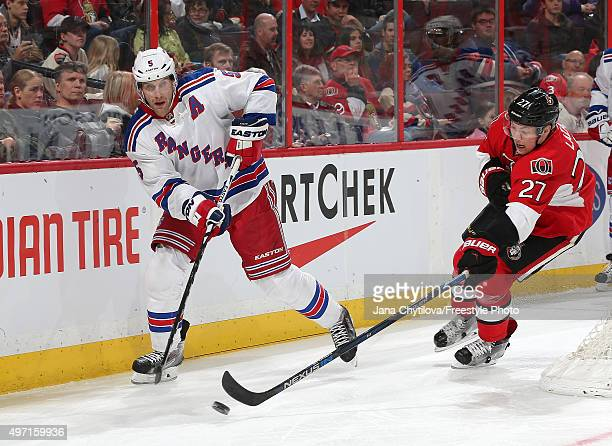 Curtis Lazar of the Ottawa Senators reaches for the puck as Dan Girardi of the New York Rangers attempts to clear it during an NHL game at Canadian...