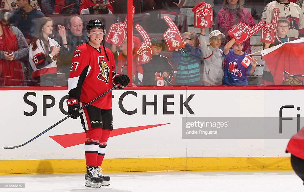 <a gi-track='captionPersonalityLinkClicked' href=/galleries/search?phrase=Curtis+Lazar&family=editorial&specificpeople=8636170 ng-click='$event.stopPropagation()'>Curtis Lazar</a> #27 of the Ottawa Senators smiles waiting for a pass during warmup prior to a game against the New Jersey Devils, as children wave foam fingers and Canadian flags behind the glass at Canadian Tire Centre on October 25, 2014 in Ottawa, Ontario, Canada.