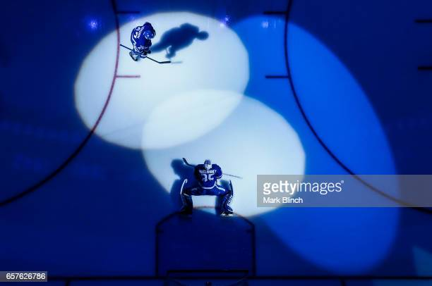 Curtis McElhinney and Leo Komarov of the Toronto Maple Leafs stretches in the spotlight prior to the game against the New Jersey Devils at the Air...
